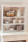 White crockery in small shelving unit on shabby-chic console table against white wooden wall