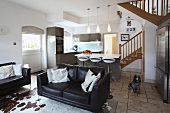Leather sofas and cow-skin rug in open-plan interior with modern fitted kitchen and country house style staircase in background