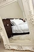 Reflexion von Doppelbett und brauner Holzkommode mit Herzchenanhänger in einem Spiegel mit weißem, aufwendig verzierten Holzrahmen