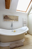 Soft beige and wood tones in white bathroom with free-standing bathtub below angled skylight