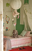 Soft toy on bed in child's bedroom with fitted wardrobe and green wall
