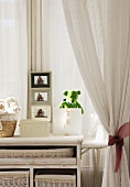 Baskets, soft toys and photos on white cabinet in front of window