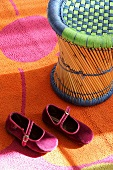 Bamboo stool and girl's shoes on colourful rug
