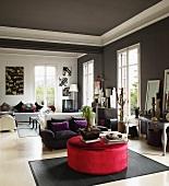 Polstertisch mit rotem Samtbezug, Sofagarnituren und hohe Fenster in einem eleganten Salon