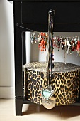 Jewellery hanging from wire above leopard-print storage box