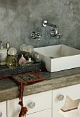 Washstand with square basin against grey partition