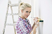 Renovating - woman with spirit level and pen
