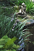 Seated stone figure amongst grasses next to pond