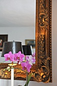 Violet orchids in front of mirror with ornate gilt frame