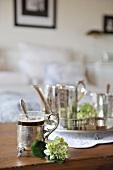 Kaffee im Glas mit verziertem Metallbehälter und Henkel neben weisser Blüte vor Tablett mit Silberservice