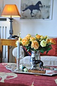 Tray with silver vase of roses and lit candle on coffee table in traditional living room