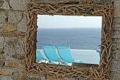 Mirror with frame made of twigs reflecting deckchairs and the sea