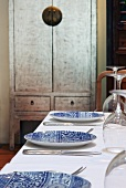Blue and white plates and cutlery on white tablecloth next to Oriental wooden cabinet against wall