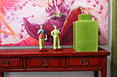 Painted china figurines next to green ceramic jar with lid on console table and colourful picture on wall