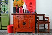 Ornaments on old Oriental cabinet in front of modern artwork and next to wooden chair in simple room