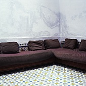 A brown corner sofa in a room with a white tiled floor