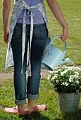 Woman in garden watering flowers