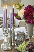 Burning candles, bunch of flowers and grapes
