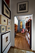 View from anteroom with gallery of pictures past bookcase in living room with parquet floor to pink Baroque chair