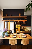Set dining table in open-plan kitchen with shelves on suspended ceiling installation painted black