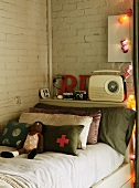 Knitted doll and stack of scatter cushions against headboard of bed below retro radio on shelf against whitewashed brick wall