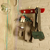 Children's clothing and bag hanging on retro coat rack on whitewashed brick wall