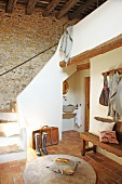 Terracotta-tiled foyer in Mediterranean country house with stone walls and rustic wooden ceiling