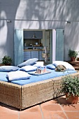 Wicker couch with blue cover and cushions on sunny terrace; view into kitchen of modern, Mediterranean house in background