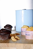Chocolate muffins and pale pastries with Spanish-printed paper cases; light blue enamel pot in background
