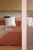 Doppelbett mit heller Tagesdecke vor den glatten Holzfronten eines Einbaumöbels; Ausschnitt einer Schiebetür mit transluzentem Bambusvorhang