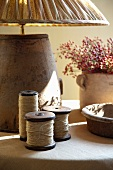 Vintage reels of yarn and rustic table lamp on table