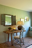 Rococo chair and rustic wooden table in front of mirror with wooden shutters on green-painted wall
