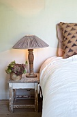 Simple bedroom with table lamp on rustic stool next to bed