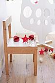Weihnachtsdeko auf einem Kinderstuhl, dahinter weisser Weihnachtsbaum aus Sperrholz