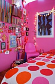 Girl's bedroom with pink walls, colourful items decorating wall and fairy lights