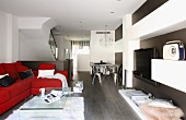 Red upholstered sofa, acrylic glass coffee table and wall-mounted shelves in designer apartment
