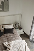 Bedroom in shades of grey with view down onto double bed with headboard and blanket