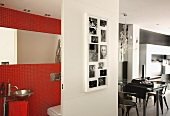 Black and white photos on sliding door in front of red-tiled guest toilet: living-dining area in background