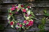 Summer wreath of hydrangeas, asters, sage and grasses hanging on wooden fence