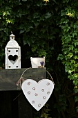 White metal heart and lantern in front of Virginia creeper in garden