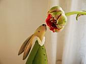 Hasenfigur schnuppert an Blume