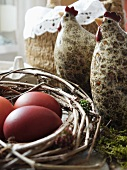 Ceramic hen figurines and brown eggs in nest