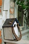 Birdhouse at timber-framed house