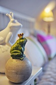 Frog figurine with crown sitting on ball