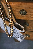 Handbag and necklace hanging at dresser