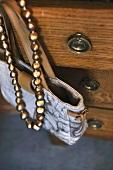 Handtasche und Kette hängen an einer Kommode