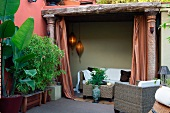 Modern outdoor wicker furniture and tropical potted plants next to sofa in Mediterranean loggia