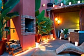 Twilight atmosphere on Mediterranean terrace with lit lanterns and light rope next to house with red lime washed facade