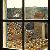View through lattice window of chimney and Mediterranean roof with monk and nun tiles