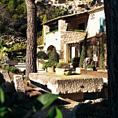Mediterranean house complex and terrace seating area with weathered stone table top in front of mountain rock face
